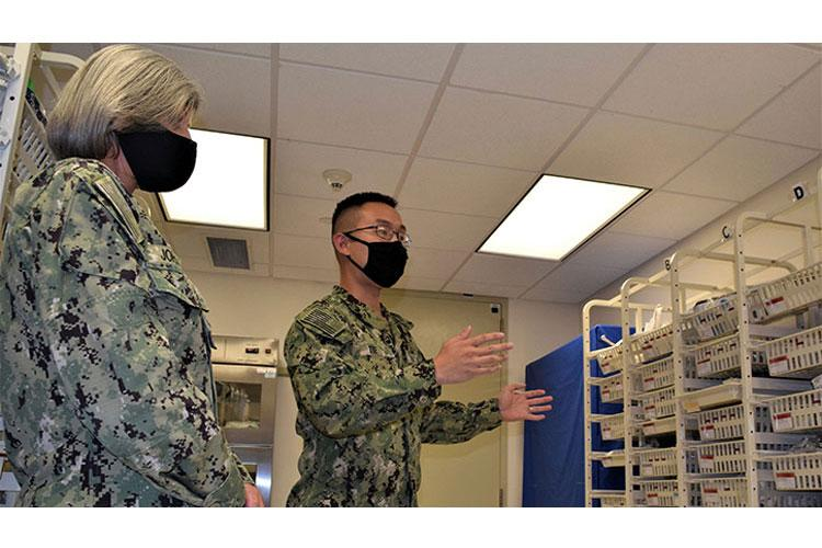 Navy Hospitalman Paul Tie, assigned to Naval Hospital Bremerton's (NHB) Multi Service Unit explains to Navy Capt. Shannon Johnson, NHB/Navy Medicine Readiness and Training Command commanding officer the recent overhaul of the unit's supply room, effectively improving access to daily needs, repositioning emergency supply resources and reallocating under-utilized stock elsewhere. (Photo by Douglas H Stutz, NHB/NMRTC Bremerton.)