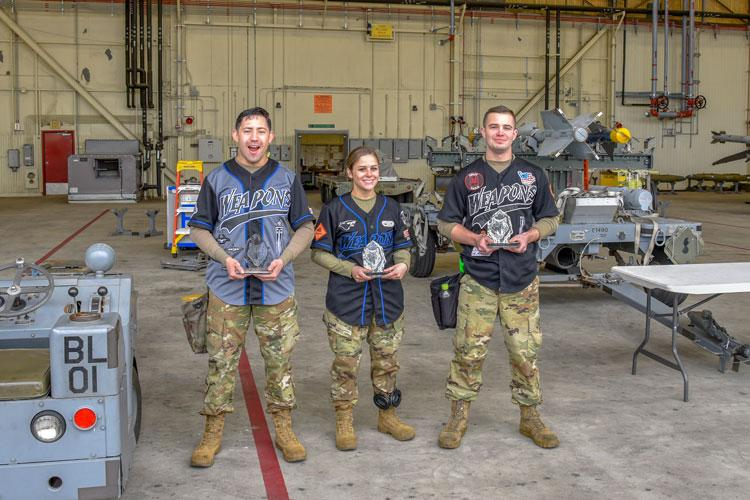 U.S. Air Force Staff Sgt. David Torres, left, Airman 1st Class Kendra Wertsbaugh, center, and Senior Airman Jayden McKenzie, right, representing the 35th Aircraft Maintenance Unit, are awarded trophies for winning the 8th Maintenance Group's Weapons Load Crew of the Year Competition at Kunsan Air Base, Republic of Korea, Jan. 25, 2020. The three-person crews were evaluated on safety, reliability, technical proficiency and time. (U.S. Air Force photo by Tech. Sgt. Joshua Arends)