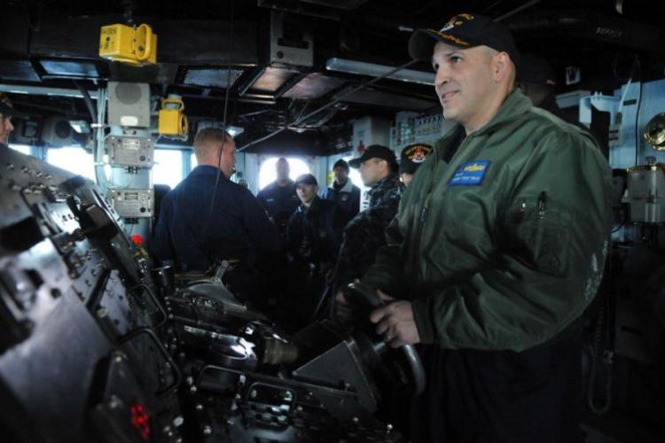Cmdr. Dennis Velez, then the commanding officer of the guided-missile destroyer USS Fitzgerald, mans the helm in the Pacific Ocean in 2011. (JENNIFER VILLALOVOS/U.S. NAVY)