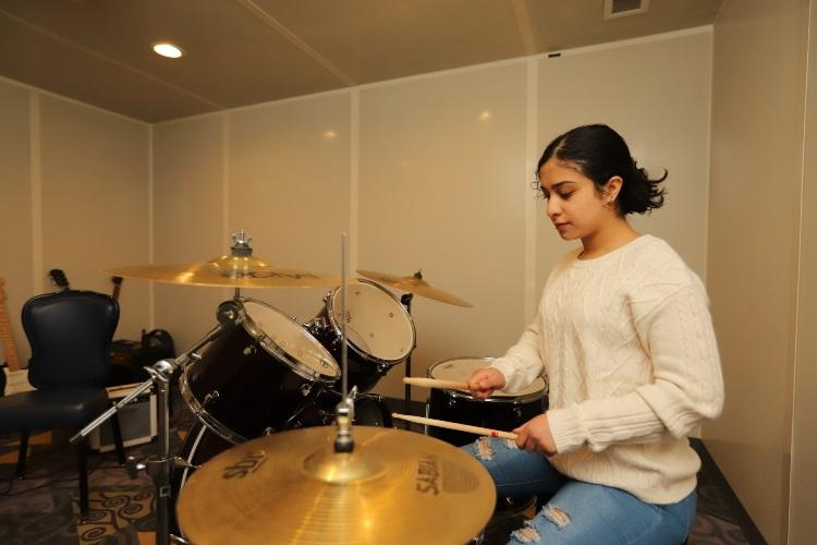 CAMP HUMPHREYS, Republic of Korea - Pfc. Dominque A. Rosales, Albuquerque, New Mexico native, wheeled mechanic, Headquarters and Headquarters Battalion, 2nd Infantry Division/ROK-U.S. Combined Division, plays acoustic drums and explores her new-found interest in music in a music rental room at the Recreation Center, March 26. (U.S. Army photo by KATUSA Cpl. Park, Seung Ho, 2ID/RUCD Public Affairs)
