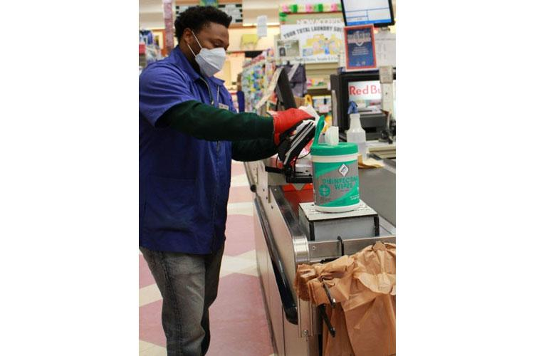 A store worker at the Daegu, South Korea, Commissary wears personal protective equipment as he wipes down a checkout area. (DeCA photo)