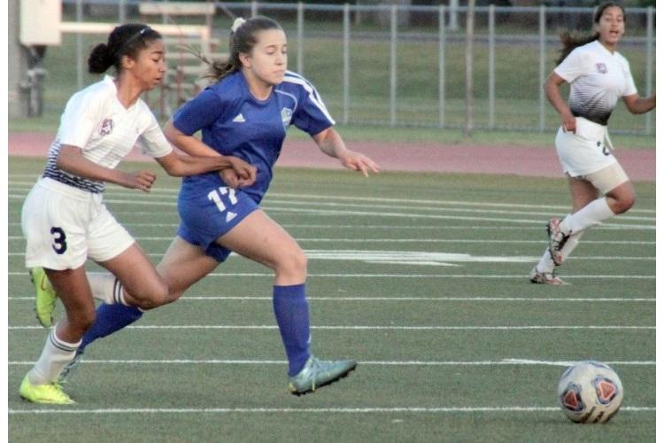 Zama's Kyleigh Rose and Yokota's Abby Schneider chase down the ball. (HANNAH MICHAEL/SPECIAL TO STRIPES)