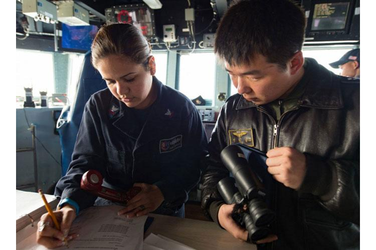 Operations Specialist 2nd Class Diana Espinoza, assigned to Destroyer Squadron 15, communicates ship movements with a South Korean navy sailor during Foal Eagle 2017. (JEREMY GRAHAM/U.S. NAVY)