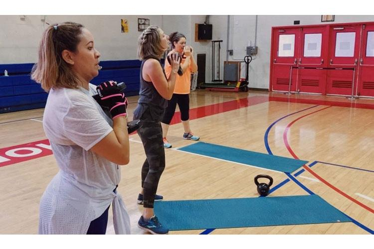 Fitness Infusion participants perform kettlebell goblet squats with weights of their choice. The exercises target every single muscle in the body with a mix of cardiovascular to improve endurance.  (Photo Credit: Laura Lee)