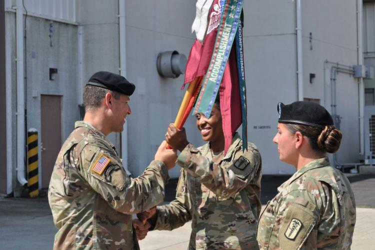 Lt. Col. Marc R. Welde, left, commander of U.S. Army Medical Materiel Center-Korea, passes a flag on Aug. 9 to Maj. Chewanda E. Jones, who takes command of the 95th Medical Detachment (Blood Support). Also pictured is Sgt. 1st Class Marina Prewitt. (Photo Credit: Chief Warrant Officer 2 Donny Puckpibul)