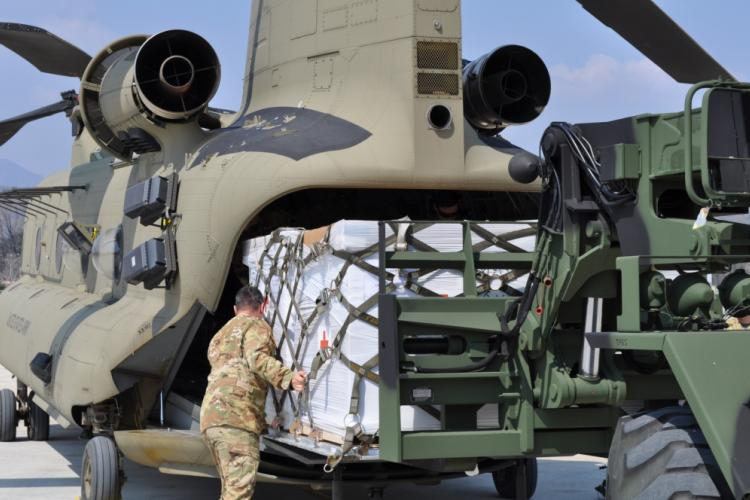 Soldiers from the U.S. Army Medical Materiel Center-Korea's 563rd Medical Logistics Company loads Class VIII medical supplies onto a CH-47 helicopter with guidance from the 2ID/2CAB crew chief on March 24, 2020. (U.S. Army photo by Shawn Hardiek