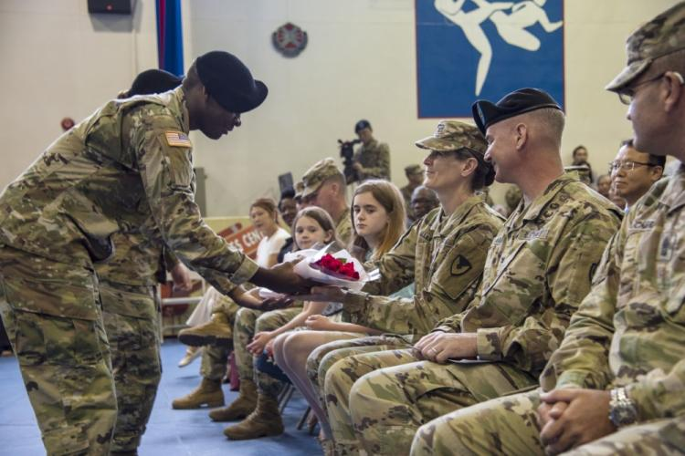 Spc. Paul Wilson presents Col. Renee Mann, commander, 403rd Army Field Support Brigade, with a bouquet of red roses during a Change of Command ceremony June 25, 2019, Camp Walker, Republic of Korea. The roses were in full bloom to signify the end of a great relationship and serves as a token of gratitude from the U.S. Army Garrison Daegu Soldiers, civilians, and their Families. (Army Photo by Pfc. Edwin Petzke, 20th Public Affairs Detachment)