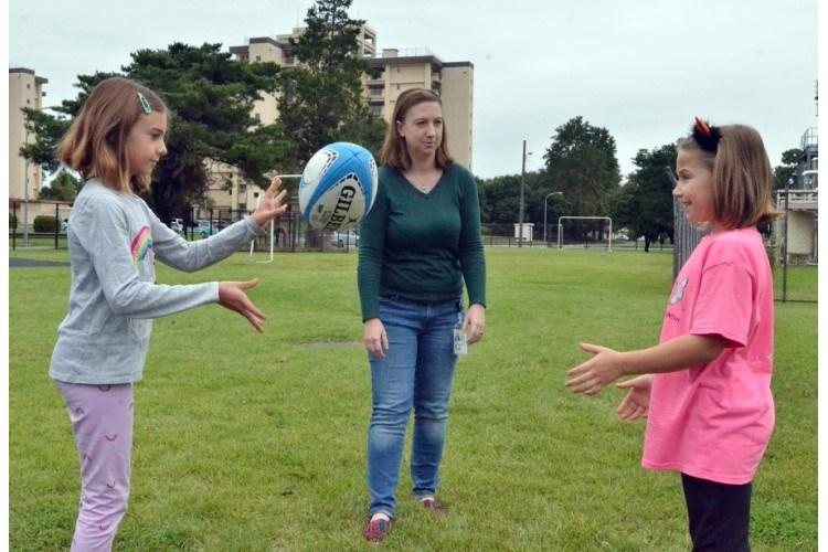 Teacher Katherine Ericson watches students Katie Petty, left, and Emery Horne toss a rugby ball outside Yokota West Elementary School at Yokota Air Base, Japan, Friday, Oct. 18, 2019. Ericson brought a group of English rugby players to the school to teach about the challenges faced by those with visual impairments. (SETH ROBSON/STARS AND STRIPES)