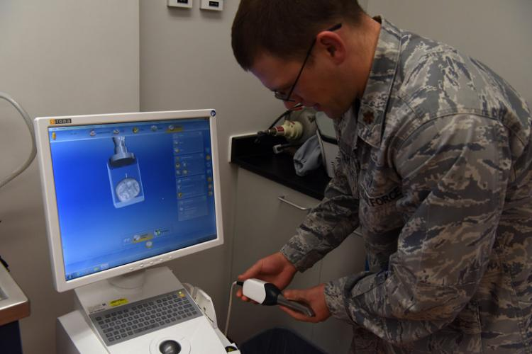 U.S. Air Force Maj. Samuel Durham, 8th Medical Group Dental Flight commander, prepares the Chairside Economical Restoration of Esthetic Ceramics machine at the dental building on Kunsan Air Base, Jan. 20, 2019. The CEREC machines photographs the mouth and creates a 3-D replica, which dentist can use to create an accurate crown of cap. (U.S. Air Force photo by Staff Sgt. Joshua Edwards)