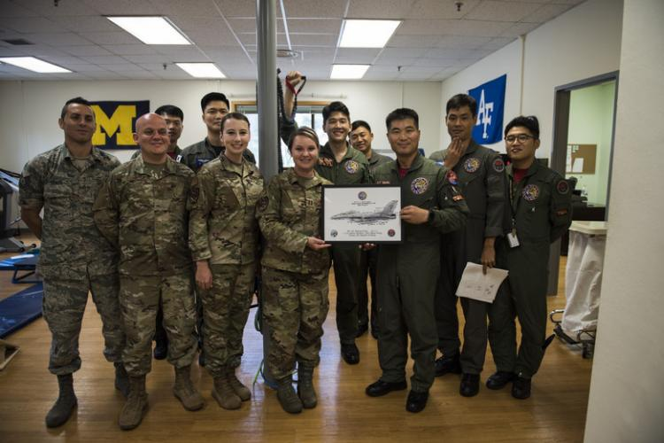 The 8th Medical Operations Squadron physical therapy flight poses with a picture with pilots from the Republic of Korea Air Force's 111th Fighter Squadron after a training session at Kunsan Air Base, Republic of Korea, Aug. 09, 2019. The 8th MDOS physical therapy flight taught the 111th FS pilots how to perform various stretches and exercises to alleviate pain and discomfort they were having. (U.S. Air Force photo by Senior Airman Stefan Alvarez)