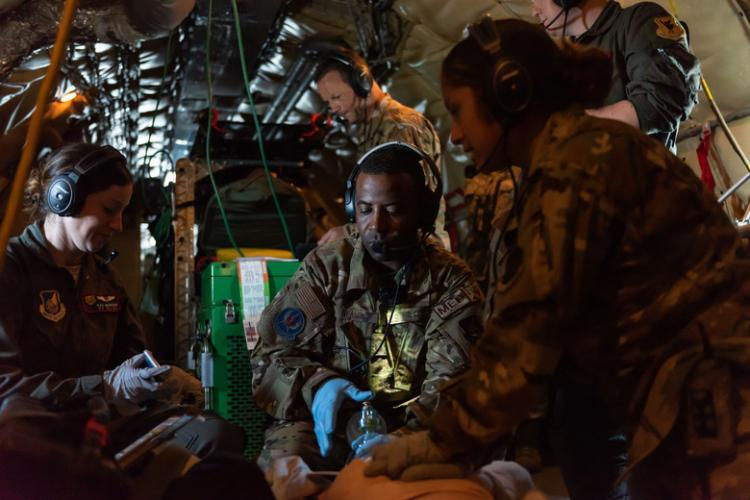 Airmen from the 18th Aeromedical Evacuation Squadron simulate life-saving procedures to a training mannequin onboard a KC-135 Stratotanker during an exercise at Kadena Air Base, Japan, Oct. 8, 2019. The 18th AES deploys and operates elements of a theater aeromedical evacuation system capable of worldwide taskings. (U.S. Air Force photo by Senior Airman Matthew Seefeldt)