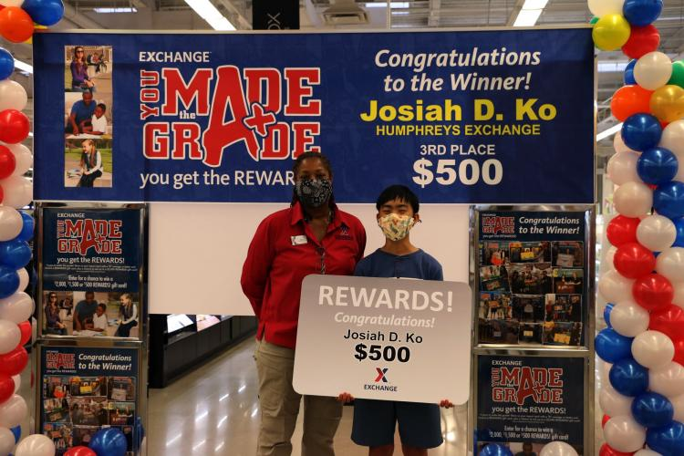 On Aug. 3, Josiah Ko, 6th grader at Camp Humphreys Middle School, receives his 3rd place, $500 Exchange gift card for his academic success in the Exchange's You Made the Grade Program from Humphrey' Main Store Manager Debra Melton, and Regional Vice President Scott Bonner during a presentation ceremony. The YMTG program is one of many ways the Exchange gives back to the community because they realize that children serve too. Exchange Photo by Mun, Yong Chin