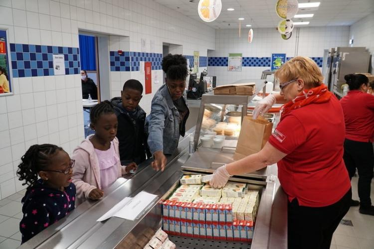 Sonja Gages, Army & Air Force Exchange Service School Meal Program manager for the Kaiserslautern Military Community district, prepares grab-and-go meals for military spouse Jovonna Nelson and her family at Ramstein Intermediate School in Germany. (U.S. Army photo by Staff Sgt. Taresha Hill) Read more: wp.me/p9Q7PG-1jk