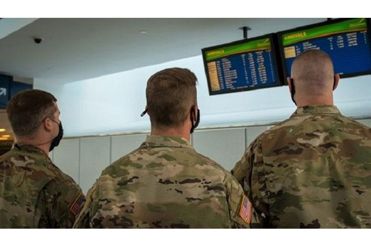 Soldiers assigned to 105th Military Police Company, Buffalo, New York, check the arrival boards at Buffalo-Niagara International Airport, supporting the state's October travel advisory. The team meets arriving passengers to distribute the State Department of Health Traveler form to travelers coming from restricted states. (Air Force photo by Master Sgt. Brandy Fowler)