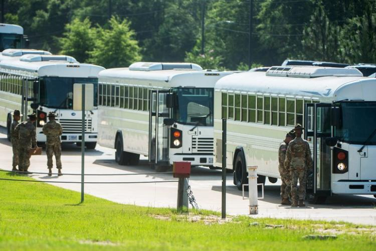In a June, 2018 photo, drill sergeants at Fort Benning, Ga., stand by as busloads of new recruits pull in to start entry level training. U.S. ARMY