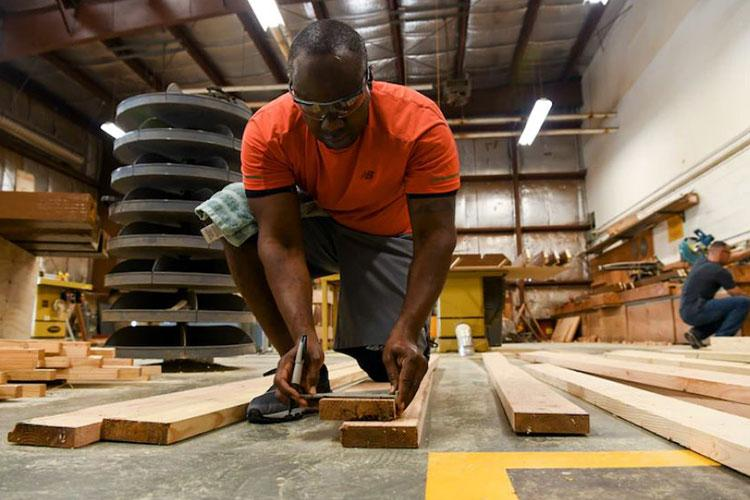 U.S. Air Force Tech Sgt. David Cameron, 8th Civil Engineer Squadron noncommissioned officer in charge of the fuels lab craft, measures refurbished wood planks at Kunsan Air Base, Republic of Korea, Aug 28, 2021. Volunteers from across the Wolf Pack dedicated hours of woodworking, gardening, painting and more to ensure the Kunsan Air Base Legacy Garden was built and dedicated to veterans by Sept 8, 2021. (U.S. Air Force photo by Staff Sgt. Jesenia Landaverde)