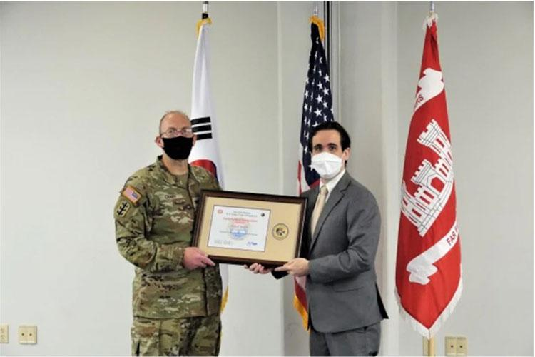 Dennis Headrick receives a certificate of recognition from Far East District Commander, Col. Christopher Crary, during graduation from the U.S. Army Corps of Engineers Leadership Development Program Level 2, July 19, 2021.