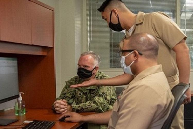 Capt. Bradford Smith, Naval Medical Center San Diego's (NMCSD) commanding officer (left), enrolls in Military Health System (MHS) GENESIS with the help of Lt. Donny Le (center) and Hospital Corpsman 2nd Class Terrance Stevens, training coordinators assigned to NMCSD. MHS GENESIS, the new electronic health record system, provides enhanced, secure technology to manage health information and integrates inpatient and outpatient solutions. (Photo by Petty Officer 3rd Class Jacob L Greenberg, Naval Medical Center