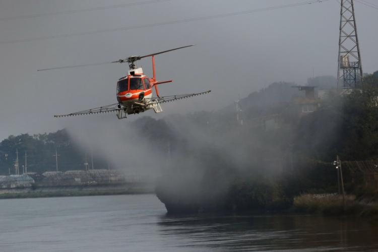 A Korea Forest Service helicopter sprays a decontamination solution to fight African swine fever near Gimpo, South Korea, Oct. 1, 2019. KOREA FOREST SERVICE