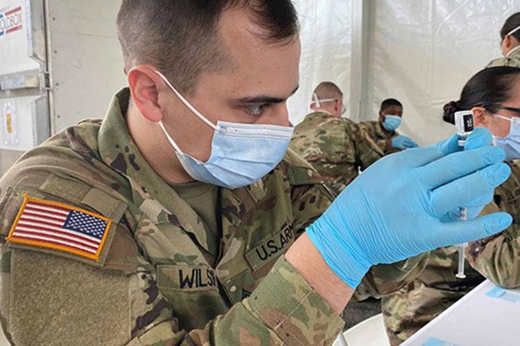 Soldiers supporting a Miami-Dade community vaccination center fill syringes with COVID-19 vaccine, March 2, 2021, in Miami, Florida (Photo by: Jocelyn Augustino, FEMA).