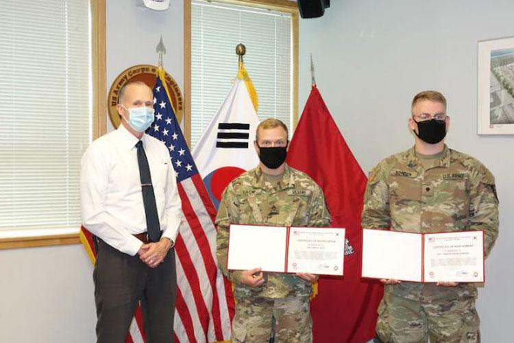 Mr. Richard T. Byrd, FED Deputy District Engineer, presents ENFIRE instructors Staff Sgt. William Lack and Spc. Christopher Bowden of the 11th Engineers with certificates of achievement.