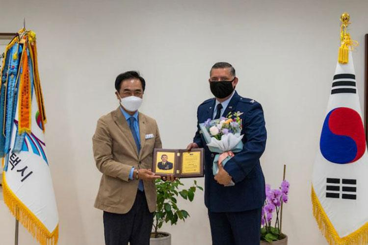 Jang Seon Jung, Pyeongtaek mayor, left, awards Col. John Gonzales, 51st Fighter Wing commander, with honorary Pyeongtaek citizenship and flower bouquet at Pyeongtaek City, Republic of Korea, May 25, 2021. This ceremony commemorated the ongoing partnership between Osan Air Base and the city of Pyeongtaek. (U.S. Air Force photo by Staff Sgt. Douglas Lorance)
