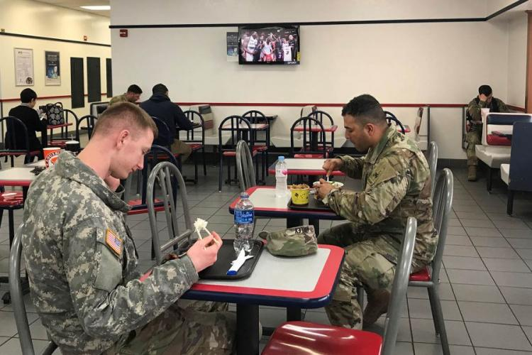 Soldiers eat lunch at the U.S. Army Garrison Yongsan food court while a TV shows sports programming Wednesday, April 10, 2019. KIM GAMEL/STARS AND STRIPES