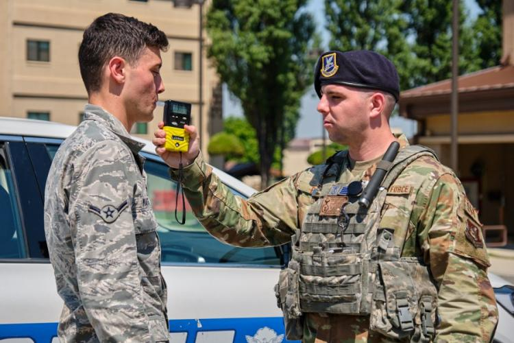 Airman Keelan Massey and Staff Sgt. Adam Bilak, both with the 51st Security Forces Squadron, train with a Breathalyzer at Osan Air Base, South Korea, Tuesday, June 25, 2019. MATTHEW KEELER/STARS AND STRIPES
