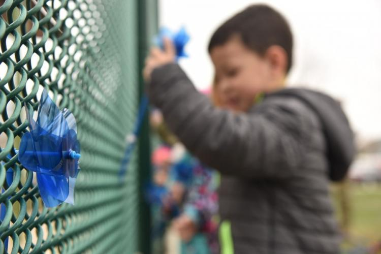 Children place pinwheels on a fence at Malmstrom Air Force Base, Mont., on April 11, 2019, during Child Abuse Prevention Month. DANIEL BROSAM/U.S. AIR FORCE