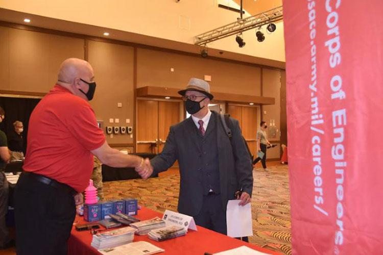 EEO Mangager, Steve Brown engages a Humphreys Job Fair attendee on the positions available with the Corps.