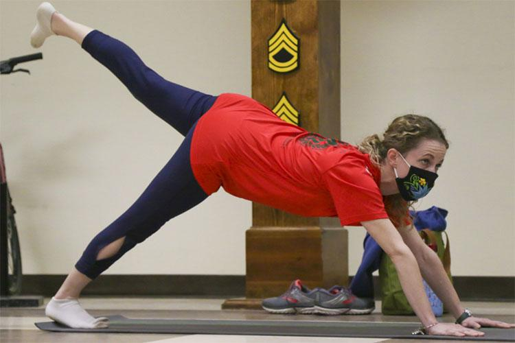 Kelly Brock, the Soldier Family Readiness Group battalion advisor for Headquarters and Headquarters Battalion, 1st Infantry Division, does yoga during an SFRG 'Yoga for Spouses' class at the HHBN headquarters building on Fort Riley, Kansas, Jan. 12, 2021. As a part of the Fort Riley SFRG's Wellness Series, the event was hosted to promote health and wellness within military spouses. (U.S. Army photo by Spc. Alvin Conley)
