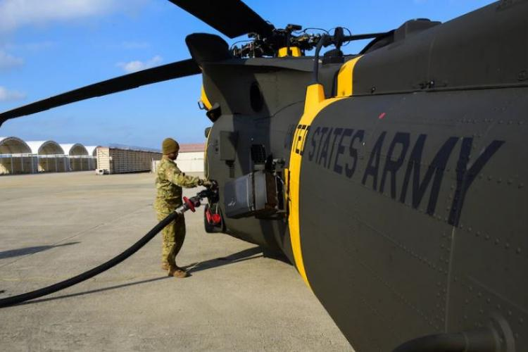 Sergeant Javian Mitchell, Charlie Company, 3-2 General Support Aviation Battalion crew chief, refuels an HH-60M Black Hawk at Kunsan Air Base, Republic of Korea, Dec. 4, 2020. The HH-60M is the U.S. Army's medical evacuation version of the UH-60M, configured for patient transport. (U.S. photo by Senior Airman Jessica Blair)