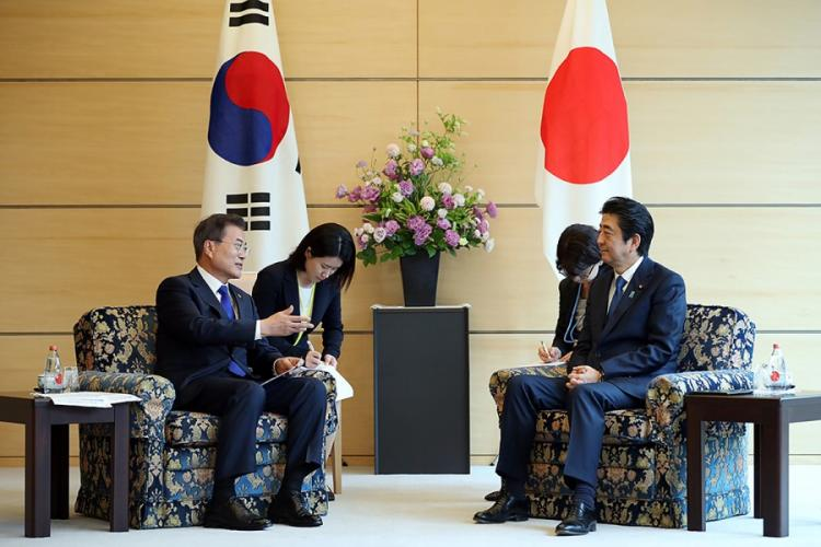 South Korean President Moon Jae-in, left, meets with Japanese Prime Minister Shinzo Abe in May 2018 before relations between the neighboring countries deteriorated this year.  CHEONG WA DAE