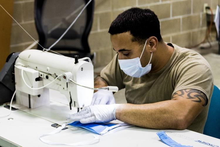 A parachute rigger with 1st Special Forces Group (Airborne), Group Support Battalion sews surgical masks for medical patients at Joint Base Lewis-McChord, Wash., on March 31, 2020. JOE PARRISH/U.S. ARMY