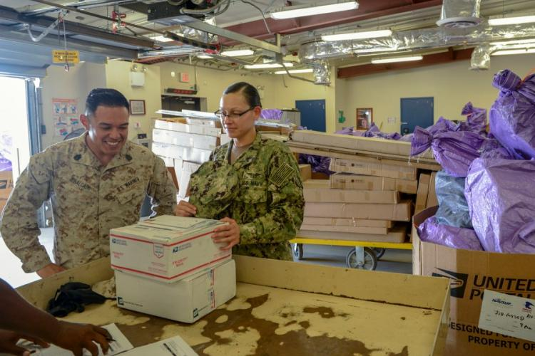Petty Officer 1st Class Alyssa Babcock, right, signs for department mail at Camp Lemonnier, Djibouti, Dec. 12, 2019. A new U.S. Postal Service policy would require everyone, including those at overseas military post offices, to fill out and print electronic customs forms, which military officials say is likely to cause customer delays. MARQUIS WHITEHEAD/U.S. NAVY