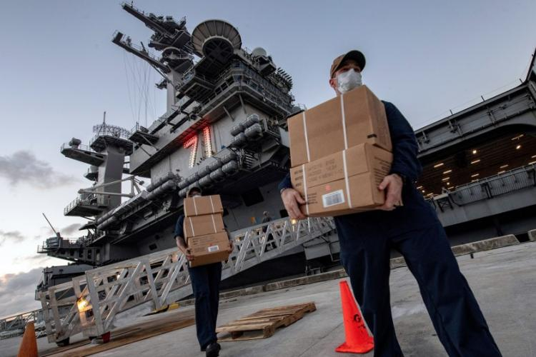 Sailors assigned to the aircraft carrier USS Theodore Roosevelt move meals, ready to eat for shipmates who have tested negative for the coronavirus at Naval Base, Guam, April 7, 2020. JULIO RIVERA/U.S. NAVY