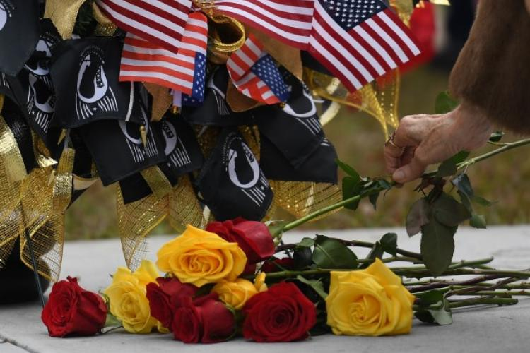 Gold Star family members place roses at the base of a wreath during the Gold Star Families Memorial Monument dedication ceremony at Guice Veterans Memorial Park in Biloxi, Miss., Nov. 23, 2019. The monument honors families of service men and women who sacrificed their lives while serving in the military. (Photo Credit: Kemberly Groue)