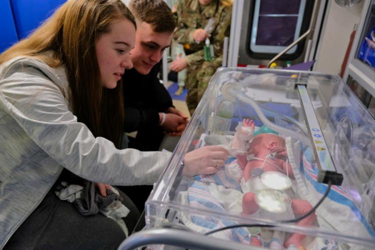 Pfc. Cheyenne Evans and her husband, Spc. Cody McFall, sit next to one of their newborn twins inside an ambulance at Osan Air Base, South Korea, Monday, March 30, 2020. MATTHEW KEELER/STARS AND STRIPES