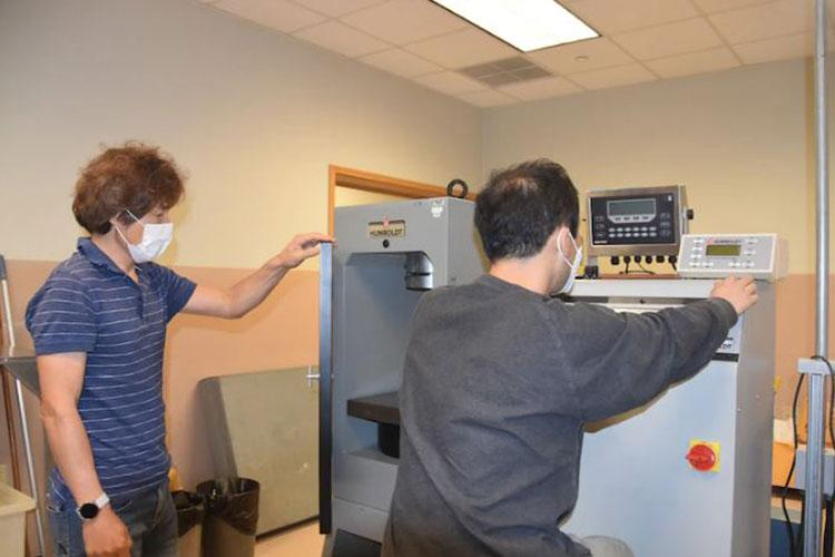 Mr. Song, Un-Ho and Mr. Choe, Chong-UK (material engineering technicians) performing tests in the Materials Testing Lab.