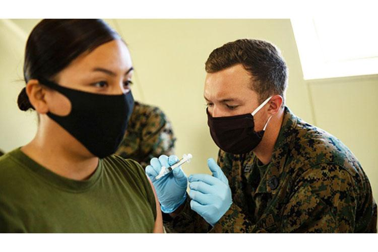 Navy Seaman Jared Doherty administers a vaccine to a Marine with the 15th Marine Expeditionary Unit during an exercise at Marine Corps Base Camp Pendleton, California, to increase theater force health protection readiness. (U.S. Marine Corps photo by Cpl. Patrick Crosley)