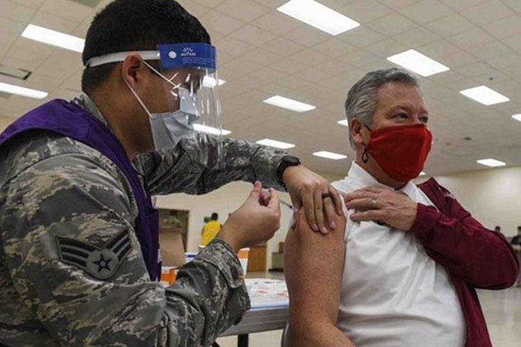 Timothy Ames (right), superintendent of the Medical Lake School District in Washington State, gets his first COVID-19 vaccination at Fairchild Air Force Base, Washington, on Jan. 21. The partnership between the district and Fairchild AFB is vital to the support and education of the military children attending schools in the MLSD (Photo by: Airman Kiaundra Miller, 92nd Air Refueling Public Affairs Wing).