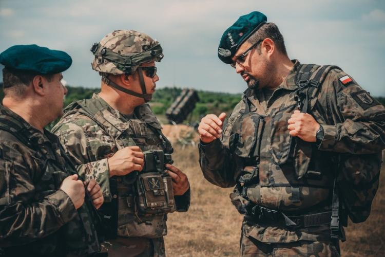 U.S. Army Chief Warrant Officer 2 Eric Land, center, assigned to 5th Battalion, 7th Air Defense Regiment, talks with Polish air defense artillery officers about the new MIM-104 Patriot surface-to-air missile system near Drawsko Pomorskiego, Poland, in June 2018. The Army is offering big bonuses to lure more warrant officers into the air defense artillery branch.  AARON GOOD/U.S. ARMY NATIONAL GUARD