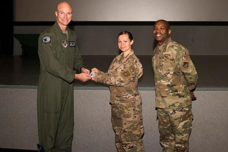 Col. Christopher Hammond, 8th Fighter Wing commander, left, and Chief Master Sgt. Ronnie Woods, 8th FW command chief, right, pose for a photo with Tech. Sgt. Sarah Hubert, 8th FW chaplain's assistant, during an all-call at Kunsan Air Base, Republic of Korea, Aug. 14, 2020. Hubert was acknowledged by Hammond due to her crisis communication skills and situational awareness that positively impacted the installation. (U.S. Air Force photo by Staff Sgt. Jordan Garner)