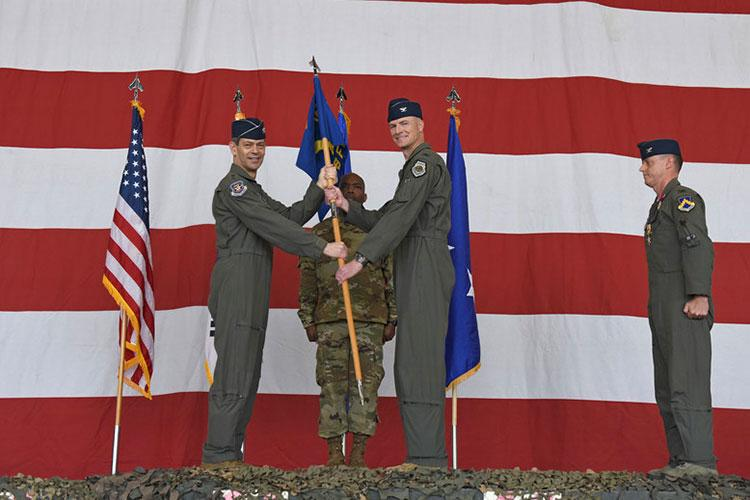 Col. Christopher Hammond, 8th Fighter Wing commander, accepts the guidon from Lt. Gen. Ken Wilsbach, 7th Air Force commander, during the 8th FW change of command ceremony at Kunsan Air Base, Republic of Korea, June 2, 2020. As Wolf 60, Hammond is responsible for more than 2,700 active-duty personnel, four groups and 13 squadrons, including two F-16 squadrons tasked with supporting 7th Air Force operational readiness. (U.S. Air Force photo by Staff Sgt. Mackenzie Mendez)