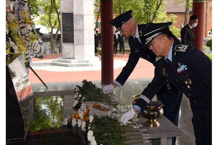 U.S. Air Force Col. Chris Hammond, 8th Fighter Wing commander, lays a white carnation to honor the fallen during the Korean Memorial Day ceremony at Gunsan City, Republic of Korea, June 6, 2020. The Korean citizens who died while serving in the military and those who lost their lives during the independence movement were honored with white carnations during the ceremony while flags and flowers were displayed at each headstone. (U.S. Air Force photo by Staff Sgt. Anthony Hetlage)