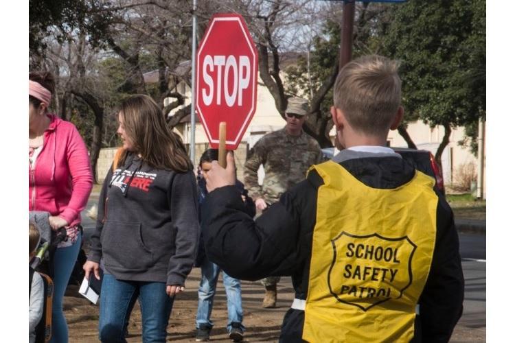 A crossing guard stops traffic for students near Joan K. Mendel Elementary School at Yokota Air Base, Japan, Friday, Feb. 28, 2020. (THERON GODBOLD/STARS AND STRIPES)