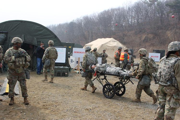 Soldiers unload a patient from a M2A3 Bradley Fighting Vehicle and transport him March 13 to 121st Combat Support Hospital's Emergency Medical Tent at Rodriguez Live Fire Complex during the Joint Combined exercise Operation Forlorn Reaper 19. (Photo Credit: Inkyeong Yun, 121st CSHBAACH)
