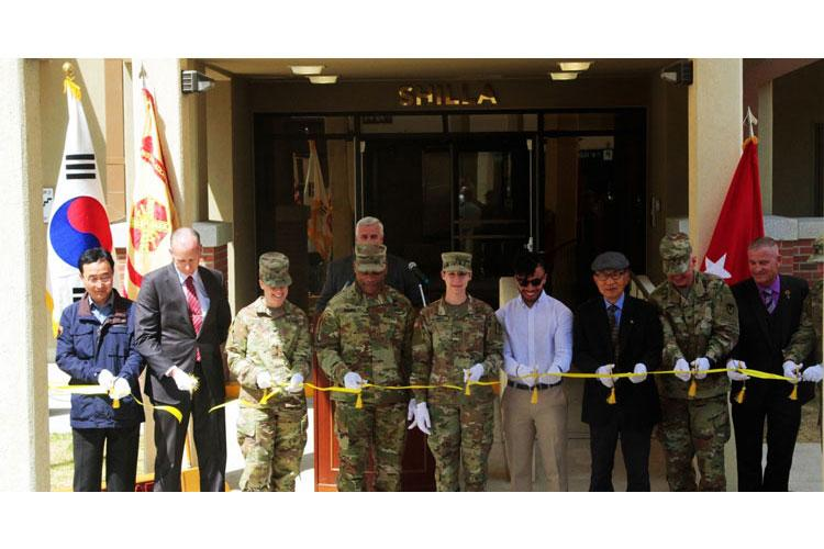 Pfc. Morgan Villarreal, radiology specialist, 168th Multipurpose Medical Brigade, and her husband Roman Villarreal along with other distinguished guests cut the ribbon for Shilla tower signifying its official opening, April 16, 2019, Camp Walker, Republic of Korea. The Villarreals are the first of many Families to be moving into Shilla tower. (U.S. Army Photo by Pvt. Jared Kindlespire) (Photo Credit: Pvt. Jared Kindlespire)