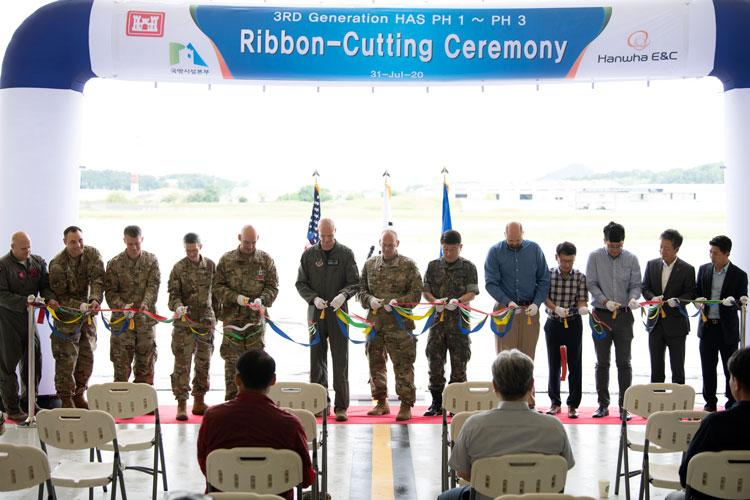 Leaders from the 8th Fighter Wing, Hanwha Engineering and Construction, Far East District, and the Republic of Korea Ministry of National Defense, cut a ribbon inside a new hardened aircraft shelter on Kunsan Air Base, Republic of Korea, July 31, 2020. The ribbon-cutting marks the completion of 20 new aircraft shelters built on Kunsan's flightline. (U.S. Air Force photo by Tech. Sgt. Will Bracy)