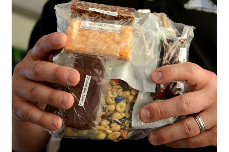 The Army is developing a new ration that uses vacuum-microwave technology to shrink items. Items under development from the Close Combat Assault Ration at the Pentagon May 24, 2018 include a root vegetable bar, Korean barbeque stir-fry package, spinach quiche, cheddar cheese bar, banana and French toast. (GARY SHEFTICK/U.S. ARMY)